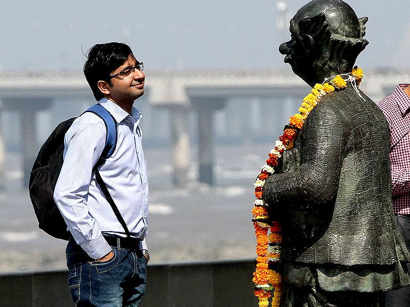 A man looks at the statue of the 'common man', created by the eminent cartoonist RK Laxman, in Mumbai. People offered floral tribute to RK Laxman who died on January 26. (Arijit Sen/HT photo)