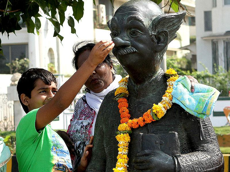 A boy looks at the statue of the 'common man', created by the eminent cartoonist RK Laxman, in Mumbai. People offered floral tribute to RK Laxman who died on January 26. (Arijit Sen/HT photo)