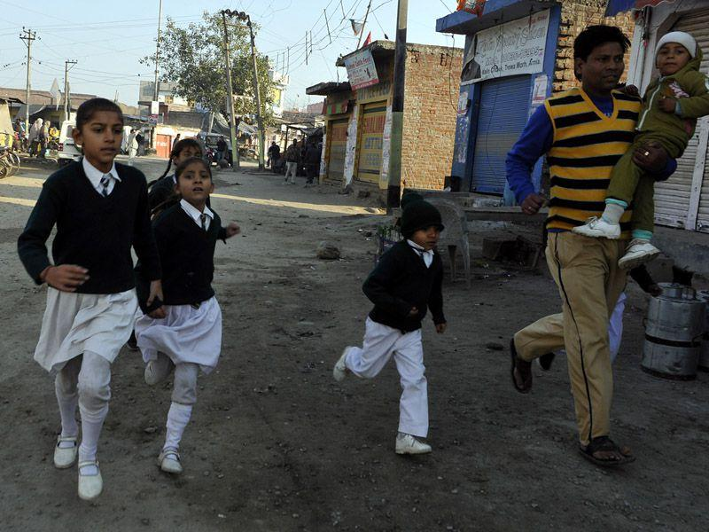 A man running along with schoolchildren to find a safer place during sudden shelling from the Pakistani side at Arnia village, about 45 km from Jammu, on Friday. Nitin Kanotra /HT