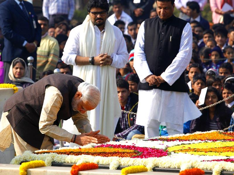 Prime Minister Narendra Modi pays homage to Mahatma Gandhi on his death anniversary as MoS Babul Supriyo looks on at Rajghat in New Delhi. (Arvind Yadav/HT Photo)