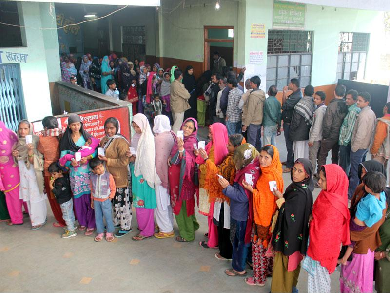 Voters stand in queue at the polling booth in Khajrana area in Indore on Saturday. (Shankar Mourya/HT photo)