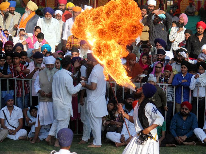 A young Sikh blows out fire from his mouth on the concluding day of a three-day religious meet in Indore on Sunday. (Shankar Mourya/HT photo)