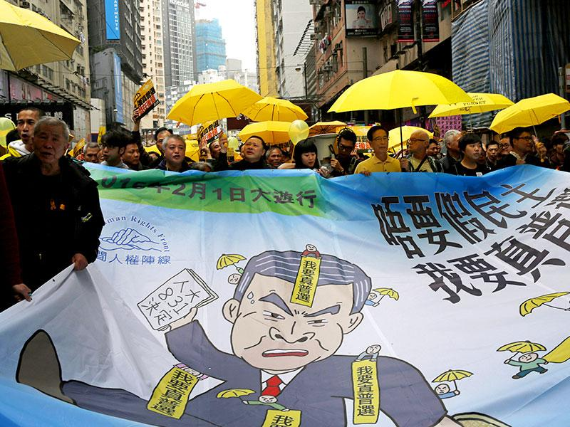 Pro-democracy activists carry a banner depicting Hong Kong chief executive Leung Chun-ying during a march to Central, demanding for universal suffrage in Hong Kong. (AP photo)