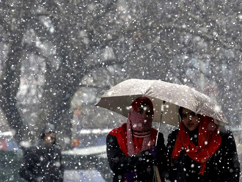 Kashmiri girls walk during a fresh snowfall in Srinagar. (HT photo/Waseem Andrabi)