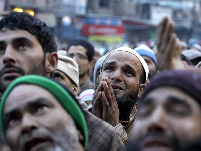 Kashmiri Muslim prays as a priest (not pictured) displays the relic of Sheikh Syed Abdul Qadir Jeelani in Srinagar. (HT photo/Waseem Andrabi)