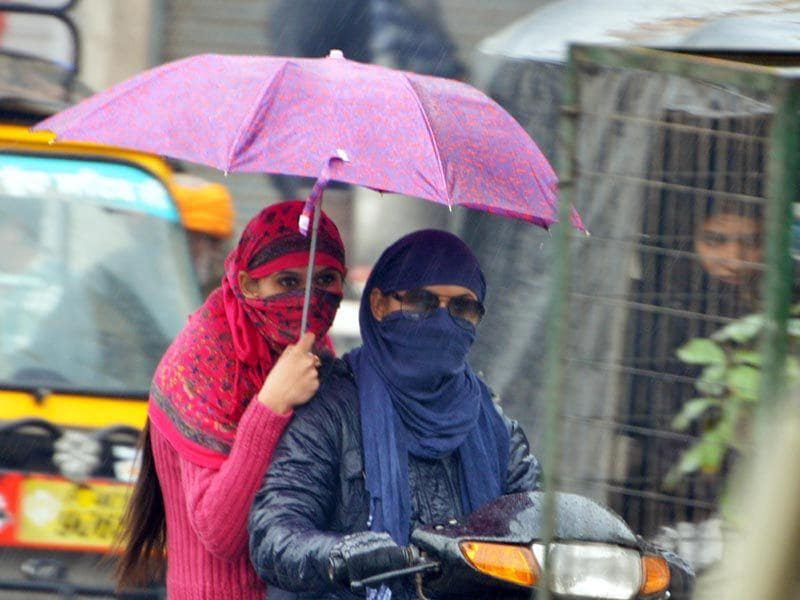 Covering themselves with umbrella, girl making way through heavy rain in Amritsar on Monday. Sameer Sehgal/HT