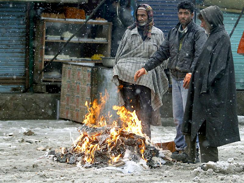 People warm themselves by a bonfire as it snows in Srinagar. Temperatures in Srinagar on Monday dipped to -1 degree Celsius (30.2 degree Fahrenheit), according to the meteorological department website. (Reuters)