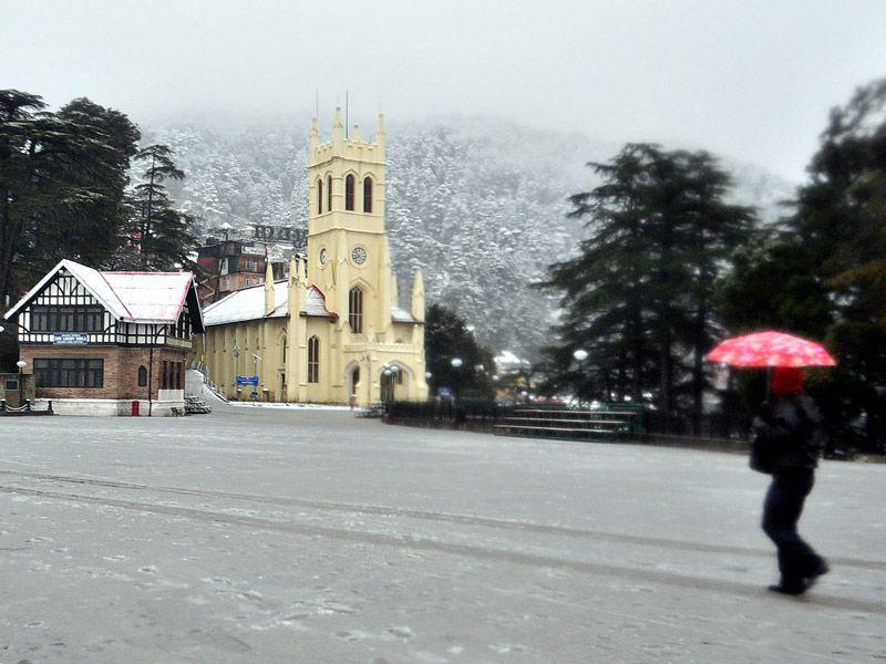 A man walking early morning in front of H.P. State library after fresh spell of snowfall at Ridge in Shimla. Santosh Rawat/HT