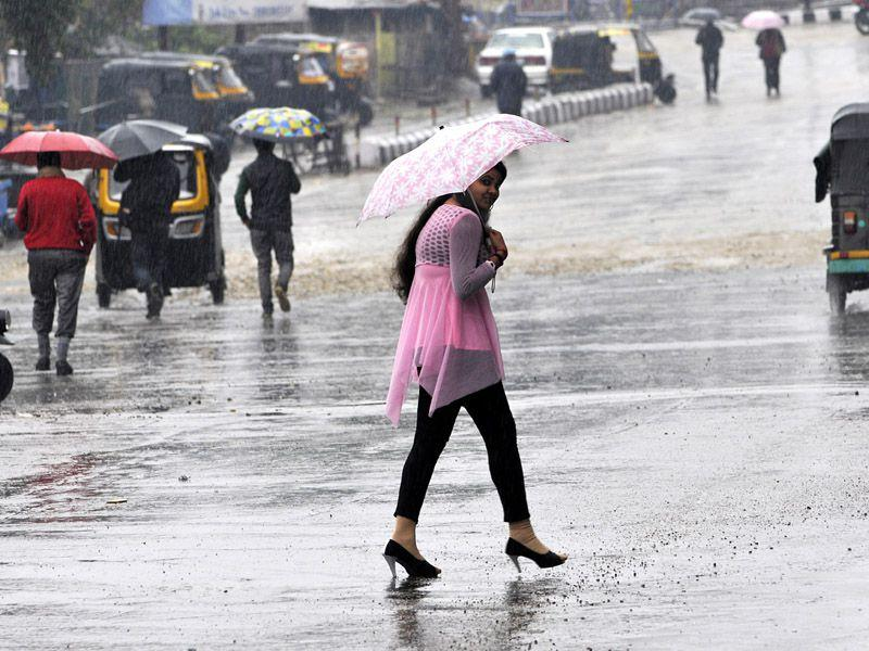 Girl shielding herself from umbrella during a rainfall in Jammu. Nitin Kanotra/HT
