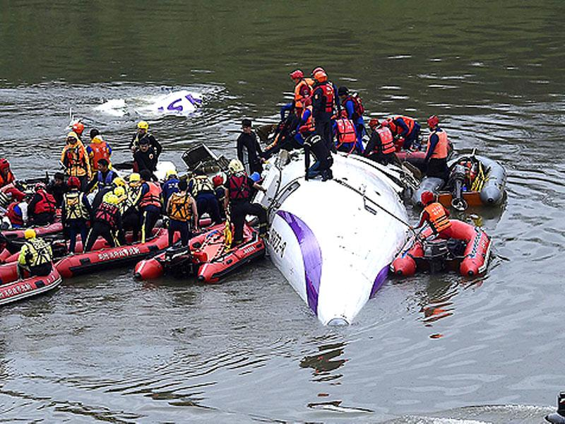 Rescuers remove a body by boat after a TransAsia Airways plane crash landed in a river in New Taipei City. (Reuters)