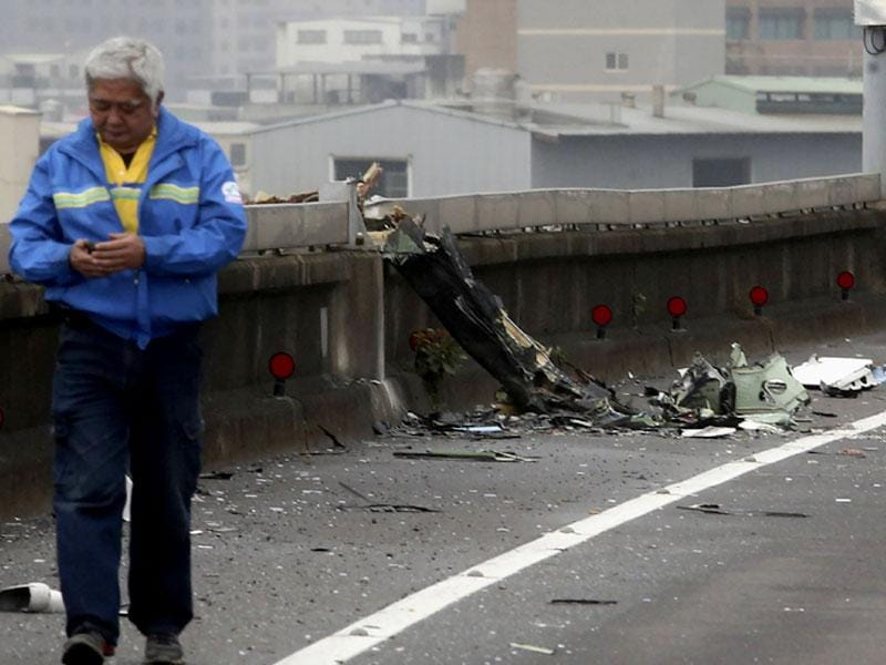 A man walks past next to the wreckage of a TransAsia Airways plane which hit a motorway before crash landing in a river, in New Taipei City. (Reuters)