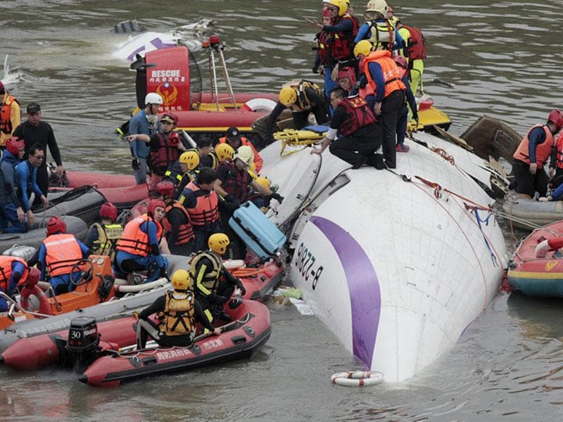 Emergency personnel try to extract passengers from the plane. (AP Photo)