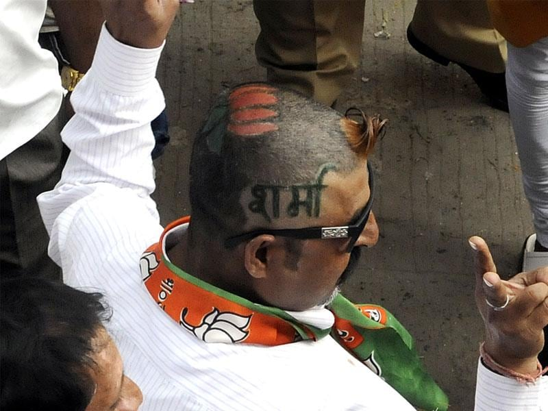 A corporator's supporter flaunts the candidate's name on his head at BJP office in Indore on Wednesday. (Arun Mondhe/HT photo)