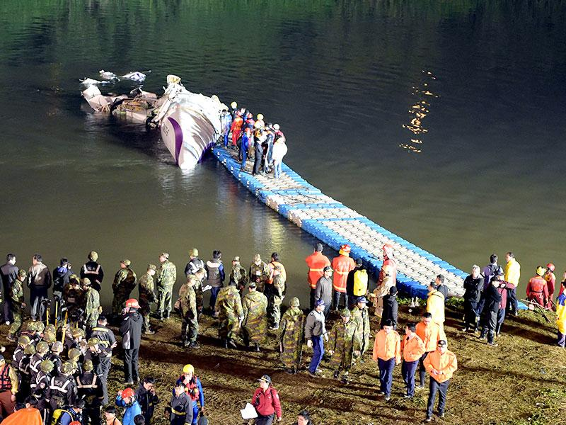 Rescuers check the wreckage of the TransAsia ATR 72-600 on the Keelung river at New Taipei City.  (AFP Photo)