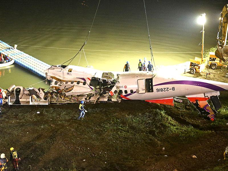 The mangled fuselage of a TransAsia Airways commercial plane is dragged to the river bank. (AP Photo)