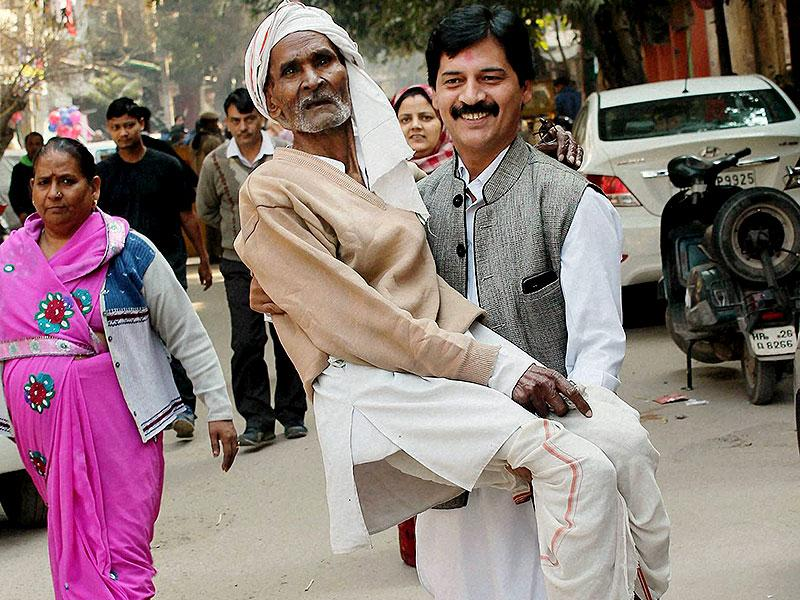 An elderly voter is carried at a polling station during voting for the Delhi assembly elections at Pul Prahladpur. (PTI Photo)