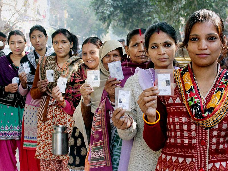 Women voters show their voter ID cards as they wait in a queue to cast their votes for the Delhi assembly elections at Pul Prahladpur. (PTI Photo)