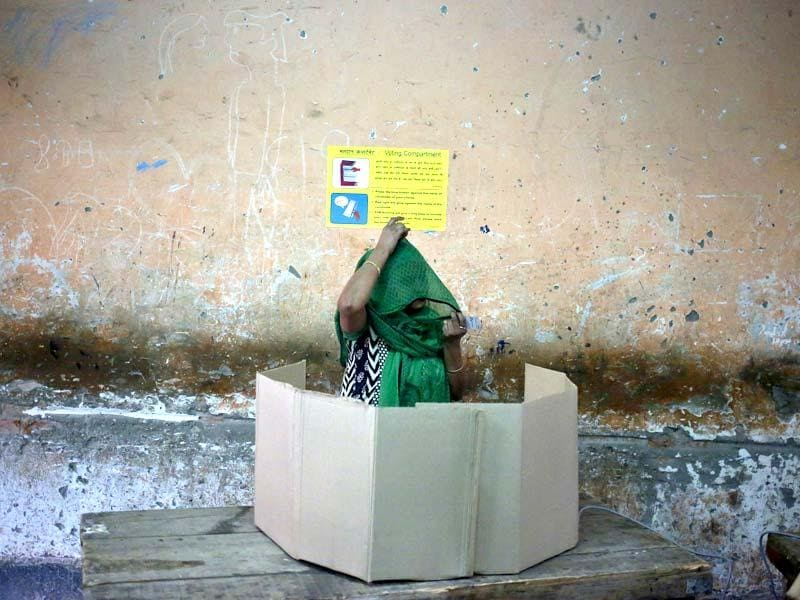 A voter prepares to cast her vote at a polling station during the state assembly election in New Delhi. (Reuters)