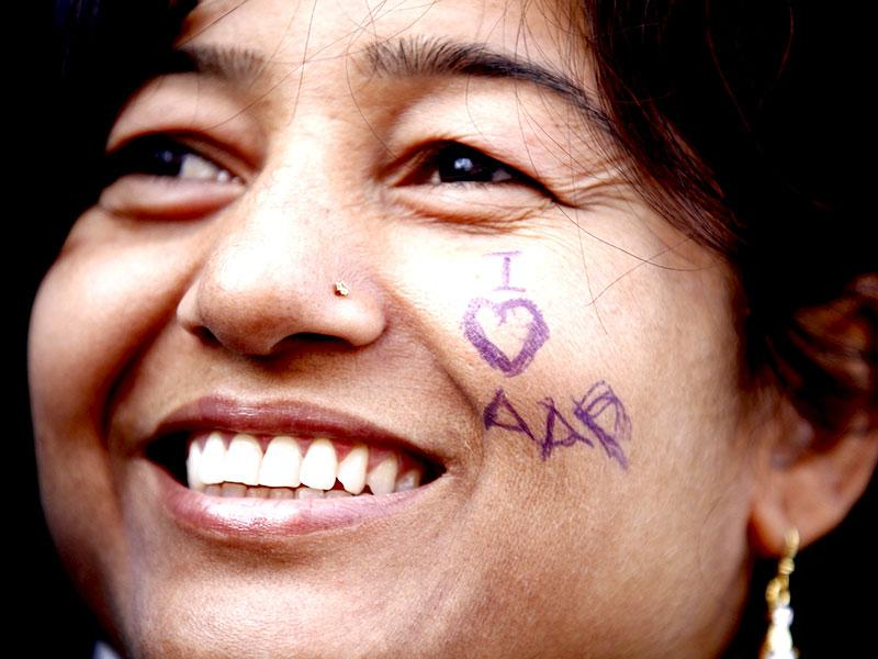 A supporter celebrates AAP's landslide win in the Delhi elections. (Ajay Aggarwal/ HT Photo)