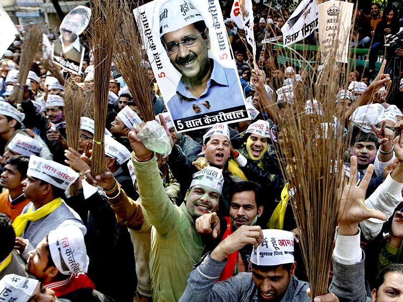 AAP volunteers wield brooms, the party's poll symbol, as they celebrate outside the Patel Nagar party office. (Arvind Yadav/ HT Photo)