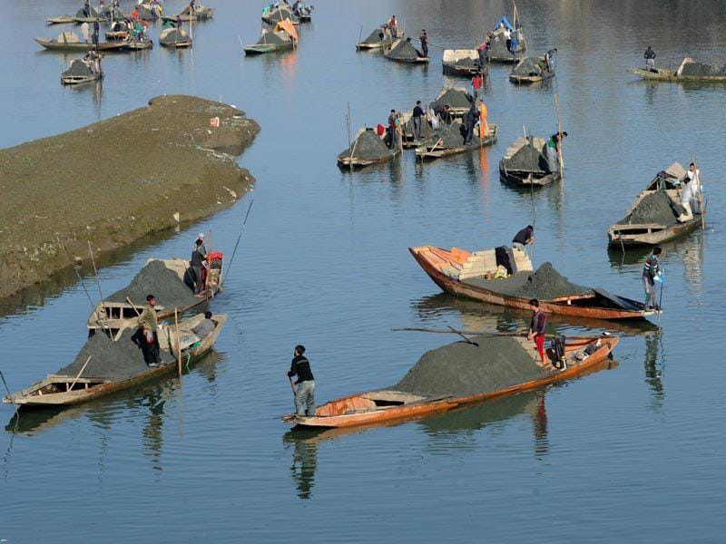 Kashmiri boatmen extract sand from the Jhelum river on the outskirts of Srinagar.The construction of residential houses continues after flash floods hit the Kashmir valley in September 2014.AFP/photo
