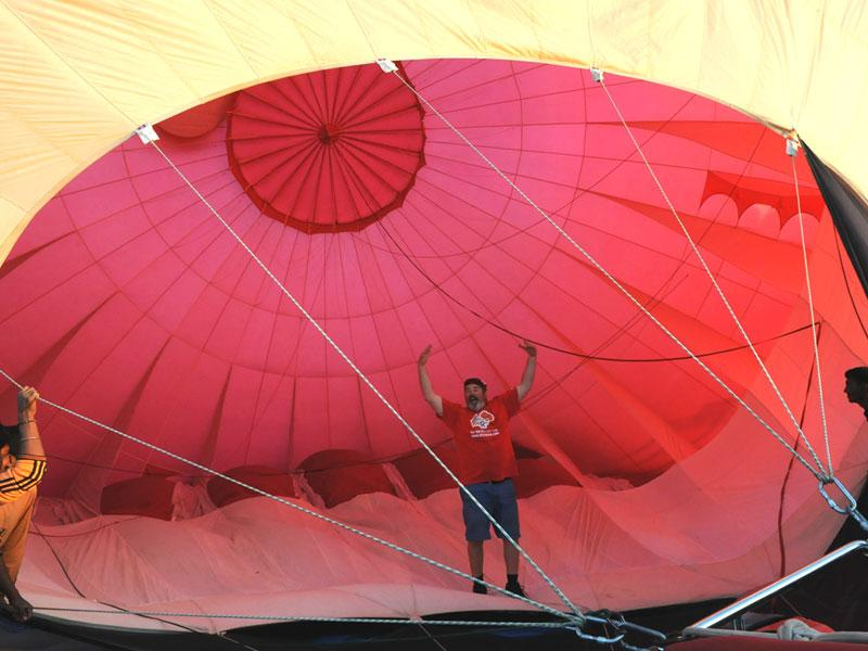 A man inflates a hot air balloon on the eve of 'Hot air balloon fest' organised as part of Bhoj adventure fest in Bhopal. (Mujeeb Faruqui/HT photo)