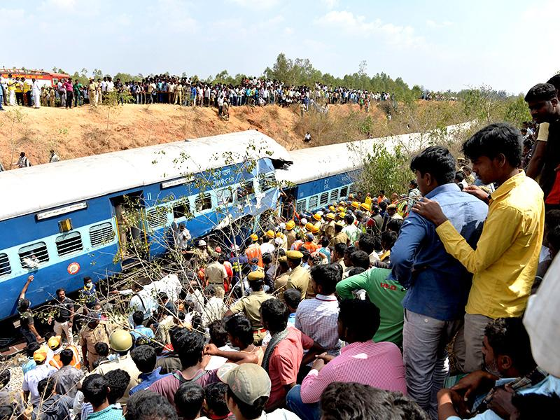 Crowds watch as firefighters attempt to retrieve the bodies of victims from the Bangalore-Ernakulam train which derailed after a boulder fell on the track in Bidaragere, about 50 kms from Bengaluru (AFP photo)