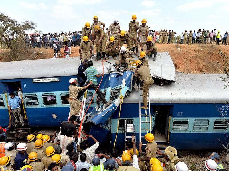 Firefighters attempt to retrieve the bodies of victims from the Bangalore-Ernakulam train which derailed after a boulder fell on the track in Bidaragere, about 50 kms from Bengaluru. (AFP photo)