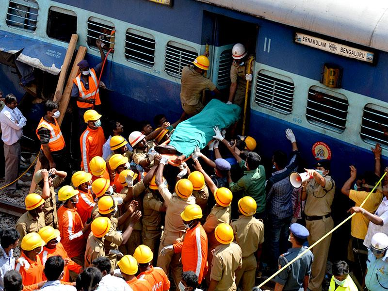 Firefighters move the body of a victim from the Bangalore-Ernakulam train which derailed after a boulder fell on the track in Bidaragere, about 50 kms from Bangalore on Friday. (AFP photo).