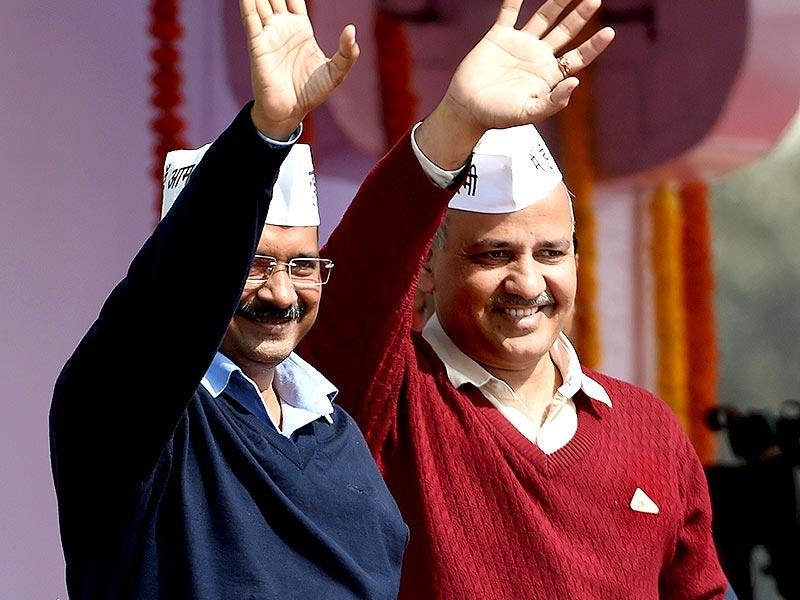 Chief minister Arvind Kejriwal (L) and Deputy CM Manish Sisodia greet supporters during the swearing-in ceremony at Ramlila Maidan in New Delhi. (AFP PHOTO)