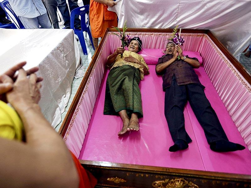 A groom and a bride lay inside a pink coffin during their wedding ceremony at Wat Takien temple in Nonthaburi province, on the outskirts of Bangkok on Valentine's Day. Ten Thai couples laid in the pink coffin during the wedding ceremony organised by the Buddhist temple on Valentine's Day. Couples believe laying briefly in the coffin will get rid of bad luck and usher happiness into their lives. (Reuters)