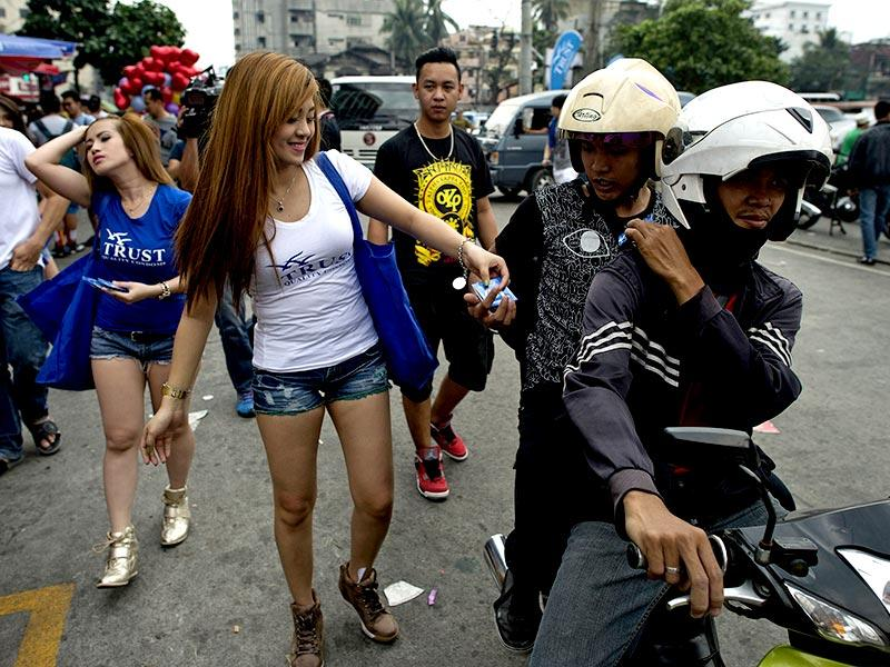 Women pass out free condoms to motorists along a street in Manila to promote safe sex on Valentine's Day. The country's biggest condom company handed out free samples to pedestrians walking on Manila's Dangwa street, but was countered by church volunteers who offered candies in exchange for the condoms. (AFP photo)