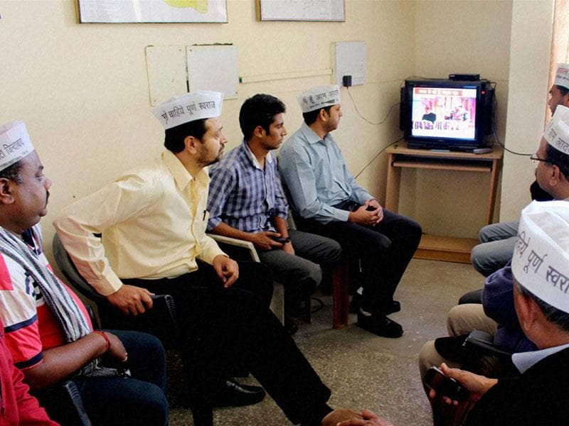 Aam Aadmi Party workers watch the live telecast of the swearing-in ceremony of Arvind Kejriwal as Delhi CM on TV, in Bhopal. (PTI photo)