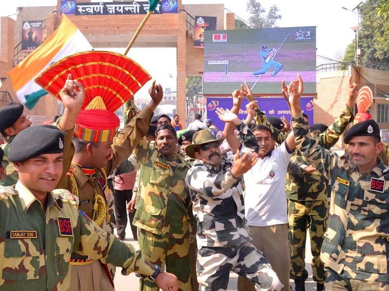 Border Security Force (BSF) personnel celebrate as they watch a live broadcast of the Cricket World Cup match between Indian and Pakistan at the Wagah Border post at Attari. (HT photo/Sameer Sehgal)