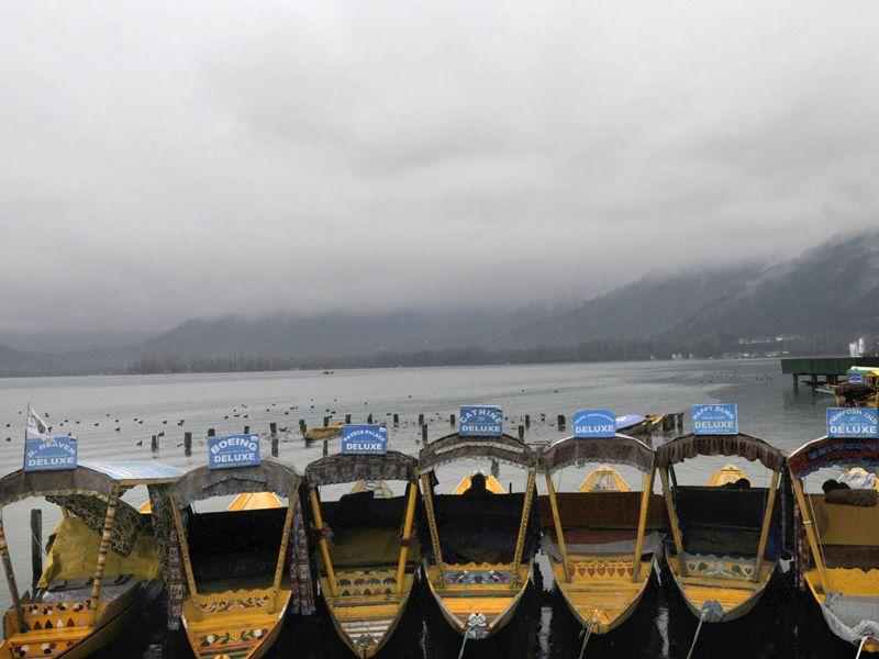 Empty traditional boats waits for tourists as rain clouds hover over the Dal Lake in Srinagar. Waseem Andrabi/HT
