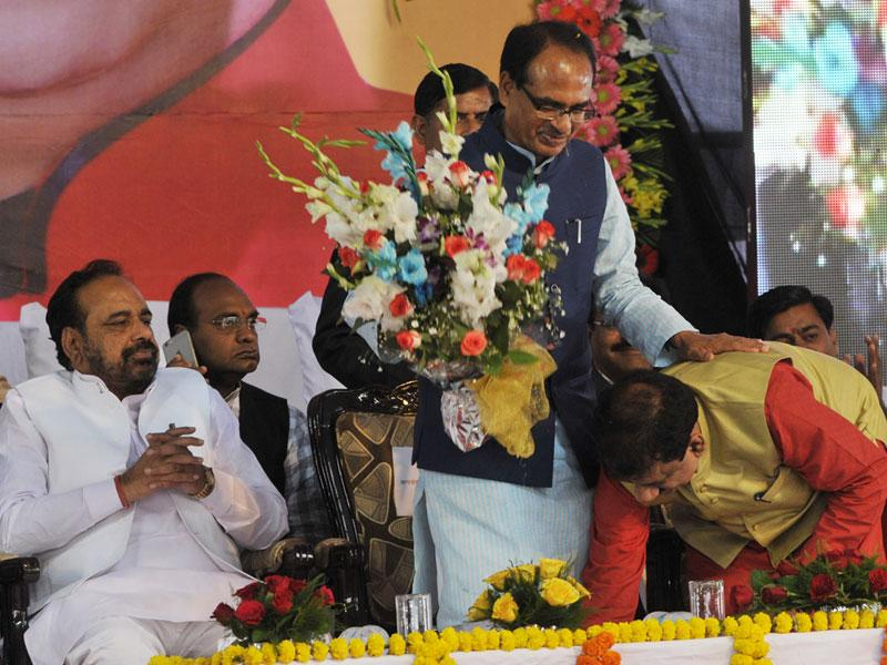 Alok Sharma touches MP chief minister Shivraj Singh Chouhan's feet before taking oath as Bhopal mayor on Monday. (Praveen Bajpai/HT photo)