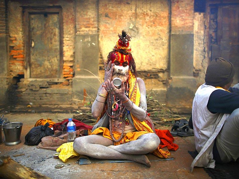 A sadhu looks into the mirror as he applies ashes on his face on the premises of Pashupatinath Temple in Kathmandu. (Reuters)