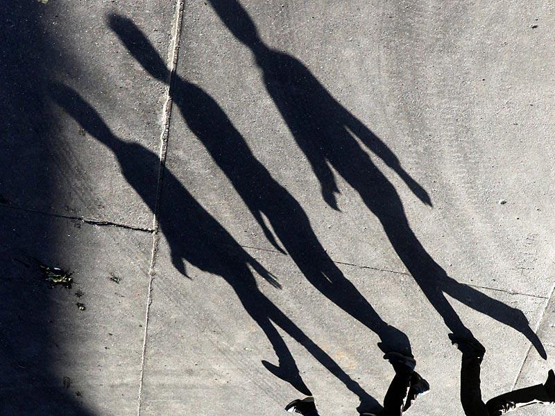 People walk as their long shadows fall on the road at Andheri in Mumbai. (Pratham Gokhale/HT Photo)