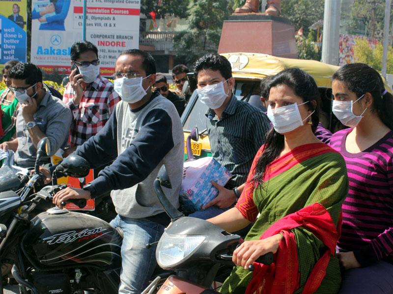 With cases of swine flu increasing, people wear masks donated by a voluntary organisation, in Indore on Tuesday. (Shankar Mourya/HT photo)