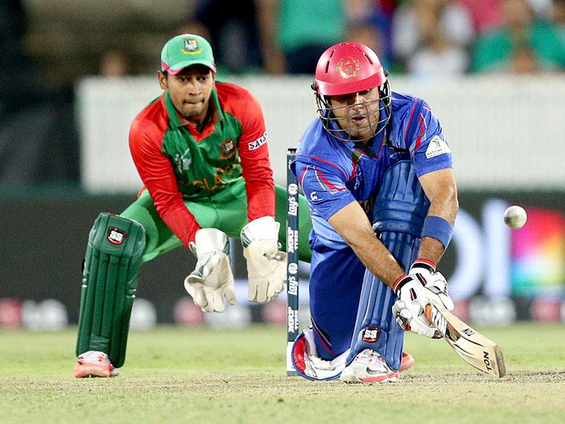 Afghanistan batsman Mohammad Nabi plays a sweep shot as Bangladesh wicketkeeper Mushfiqur Rahim looks on. (AP Photo/Rob Griffith)