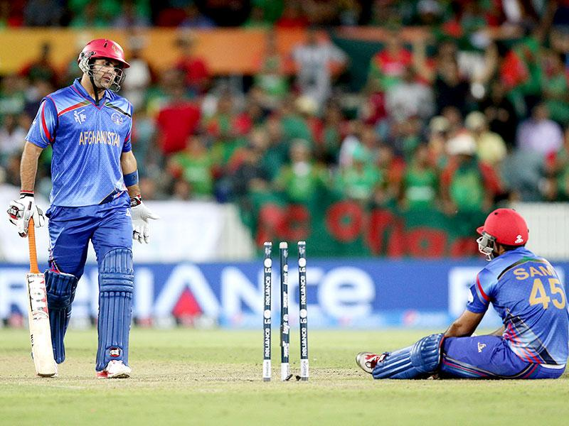 Afghanistan's Mohammad Nabi, left, talks with teammate Samiullah Shenwari as they wait for the video review of Shenwari's run out. (AP Photo/Rob Griffith)