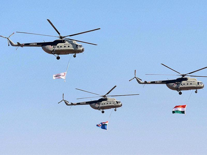 Indian Air Force helicopters fly past with Indian Tri Colour during the inauguration of the Aero India 2015. (PTI Photo)