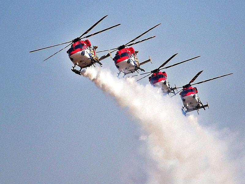 The Indian Air Forces' helicopter display team 'Sarang' performs during the inauguration of the Aero India 2015. (PTI Photo)