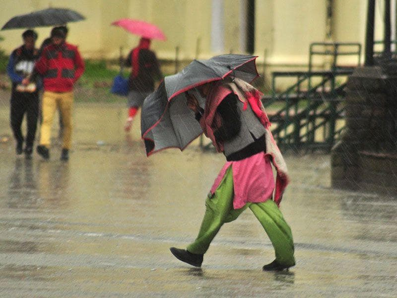 A woman braving strong wind and rain at Ridge in Shimla. Santosh Rawat/HT