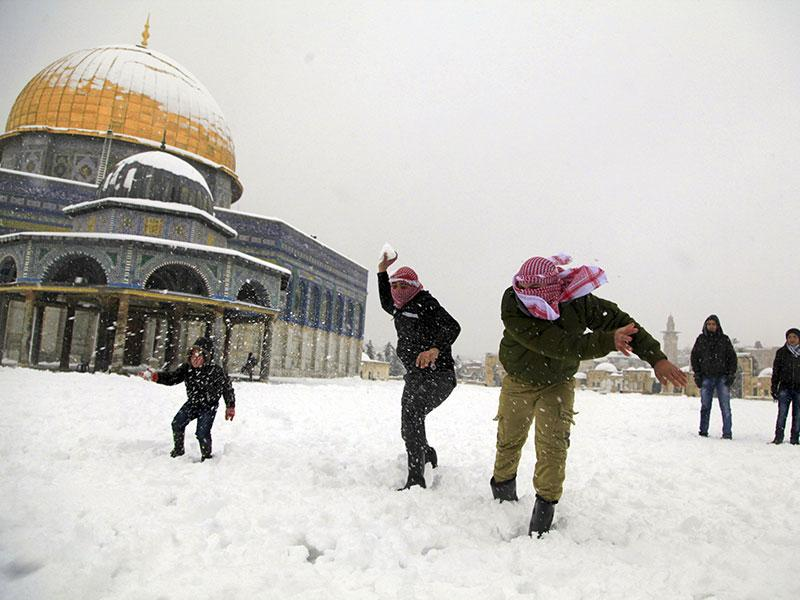 Palestinians throw snowballs in front of the Dome of the Rock in Jerusalem. A heavy winter storm descended on parts of the Middle East on Friday, with snow forcing the closure of all roads leading in and out of Jerusalem and sprinkling Israel's desert with a rare layer of white. (AP photo)