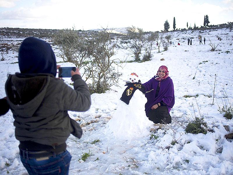A Palestinian woman poses next to a snow man in Tapuah junction in the northern West Bank, near the Palestinian city of Nablus. (AP photo)