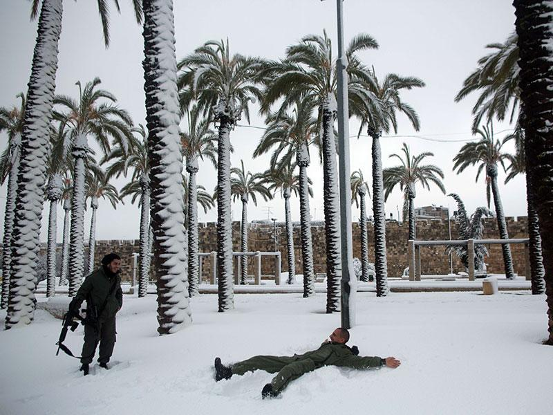 Israeli policemen play in the snow near palm trees outside Jerusalem's old cit. People in Jerusalem woke up to around 25 centimetres of snow after the second major blizzard of winter swept across the hilltop Holy City. (AFP photo)