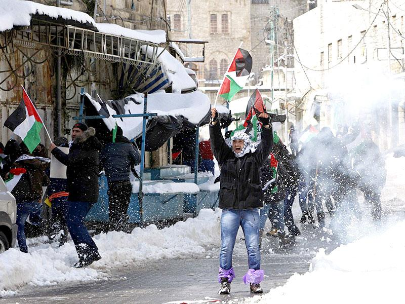 A Palestinian protester holding a Palestinian flag shouts anti-Israel slogans as snow scatters by a sound grenade thrown by Israeli soldiers during a demonstration against the closure of Shuhada street to Palestinians, in the West Bank city of Hebron. (Reuters)
