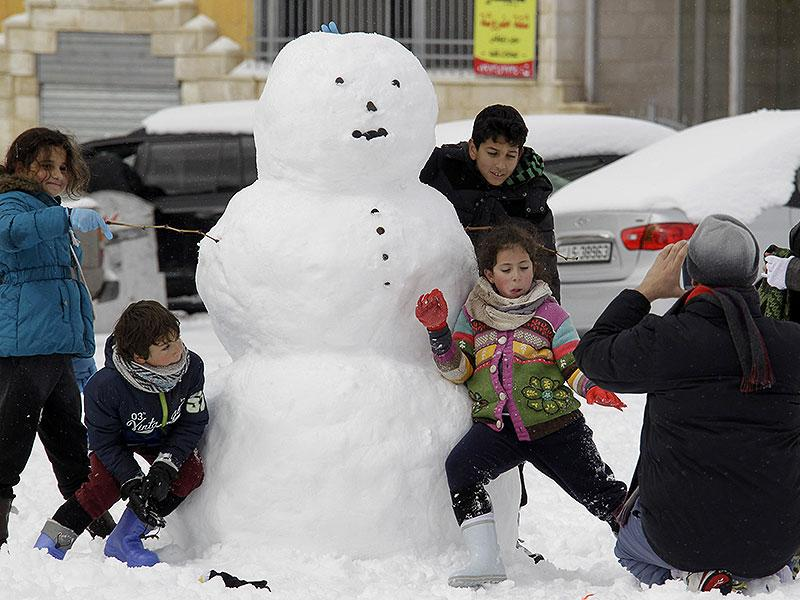 Jordanian children make a snowman in the Jordanian capital Amman. Blizzards dumped a blanket of snow over Israel, Jordan and Lebanon, with many residents urged to stay in their homes because of blocked or icy roads. (AFP photo)