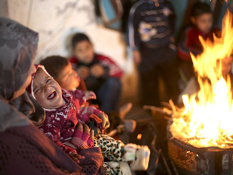 Members of a Palestinian family warm themselves by a fire at the remains of their house that witnesses said was destroyed by Israeli shelling during a 50-day war last summer, on a winter day east of Gaza City. (Reuters)